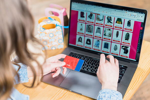 woman holding credit card front laptop with shopping website